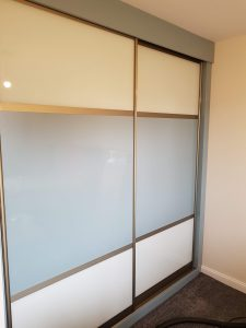 Sliding wardrobe with centre panel of blue sparkle glass and pure white top and bottom panels. Complemented by a champagne frame.